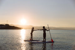 Silhouette of male and female on sup surf pull hands together at the ocean. Concept lifestyle, sport, love Stock Image