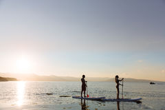 Silhouette of male and female on sup surf swimming at the ocean. Concept lifestyle, sport, love Stock Photos