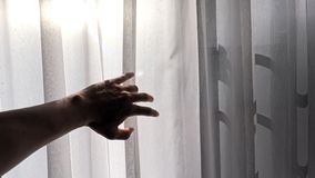 Silhouette of a male hand reaching out to the white curtain with morning sunlight effect.  stock photos