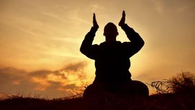 Silhouette of a male monk engaged in meditation at sunset lifestyle sunlight. Buddhist prays at sunset healthy way of. Silhouette of male monk engaged in stock footage