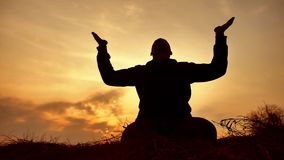 Silhouette of a male monk engaged in meditation at sunset sunlight. Buddhist lifestyle prays at sunset healthy way of. Silhouette of male monk engaged in stock footage