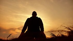 Silhouette of a male monk engaged in meditation at sunset sunlight. Buddhist prays at sunset healthy way lifestyle of. Silhouette of male monk engaged in stock footage