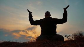 Silhouette of a male monk engaged in meditation at sunset sunlight. Buddhist prays at sunset healthy lifestyle way of. Silhouette of male monk engaged in stock video footage