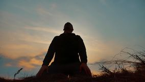 Silhouette of a male monk engaged in meditation at sunset sunlight. Buddhist prays at sunset healthy way of life. Silhouette of male monk engaged in meditation stock video footage