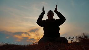 Silhouette of a male monk engaged in meditation at sunset sunlight. Buddhist prays at sunset lifestyle healthy way of. Silhouette of male monk engaged in stock video