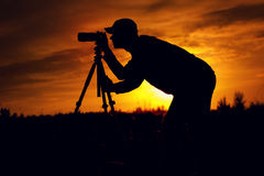 Silhouette of male photographer taking picture. Silhouette of young male photographer taking pictures with camera, standing against setting sun Royalty Free Stock Images