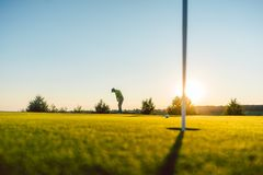 Silhouette of a male player hitting a long shot on the golf course stock photos