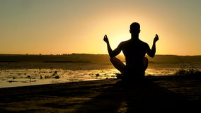 Silhouette of male practicing meditation on the beach at sunset. 4K stock footage