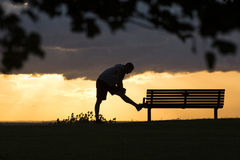 Silhouette male stretching on a bench before a run Stock Photography