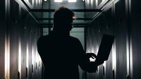Silhouette of a male technician is working in a dark server room. Male technician is working in a dark server room. 4K stock video