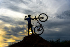 Silhouette the man in action lifting bicycle above his head stand stock photo