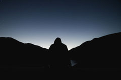 Silhouette of Man Against Mountain at Night Royalty Free Stock Photography