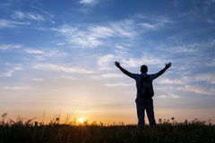 Silhouette of man with arms raised up and beautiful sky Royalty Free Stock Image