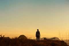 Silhouette of a man with an ax near the tent Stock Photography