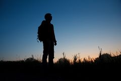 Silhouette of man with backpack against dark sky Stock Photography