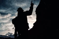 Silhouette man with a backpack in camouflage rises to the top of the mountain. Silhouette of man with a backpack in camouflage rises to the top of the mountain Stock Photos