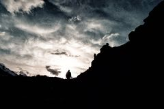 Silhouette man with a backpack in camouflage rises to the top of the mountain. Silhouette of man with a backpack in camouflage rises to the top of the mountain Stock Images