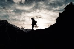 Silhouette man with a backpack in camouflage rises to the top of the mountain. Silhouette of man with a backpack in camouflage rises to the top of the mountain Royalty Free Stock Photo