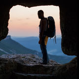 Silhouette of man with backpack in cave. Crimea Stock Image