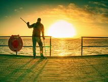 Silhouette of man with backpack on the pier on the calm sea royalty free stock images