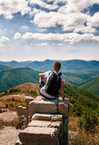 Silhouette of man with backpack sitting with his back to the photographer on the big rock and looking at the panorama of stock image