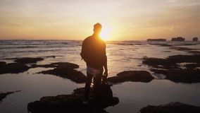 Silhouette of man with backpack standing on beach, watching beautiful gold sunset. Slow motion stock video footage