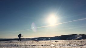 Silhouette of man with a backpack walking in a winter landscape on snowshoes. Trekking with hiking poles, blue sky and. Bright sun. Concept adventure activity stock video footage