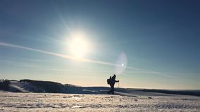 Silhouette of man with a backpack walking in a winter landscape on snowshoes. Trekking with hiking poles, blue sky and. Bright sun. Concept adventure activity stock video