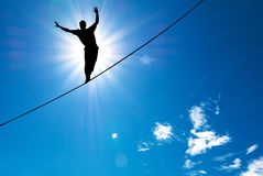 Silhouette of man balancing on the rope concept of risk taking. Man balancing on the rope concept of risk taking and challenge Royalty Free Stock Photography