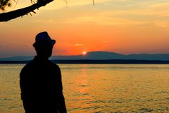 Silhouette of a man at the beautiful sunset on the Beach. Background. Young Man Looking at the Sunset. Royalty Free Stock Image