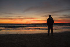 Silhouette of man on a beautiful sunset on the beach Stock Photography