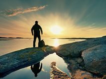 Silhouette of man. Beautiful sunset touch the sea at the horizon, clear blue sky. Hiker enjoy scenery Stock Photos
