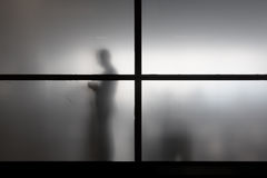 Silhouette of man behind matted glass Royalty Free Stock Image