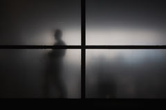 Silhouette of man behind matted glass Royalty Free Stock Photography