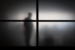Silhouette of man behind matted glass Stock Photos