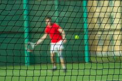 Silhouette of man behind tennis net. A man is playing tennis. A man in a red T-shirt beats a tennis ball stock photography
