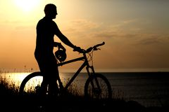 Silhouette of the man with a bicycle. At sunset Stock Image