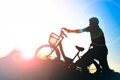 Silhouette of man with a bicycle in the park at sunset Royalty Free Stock Image