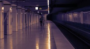 The subway station in neon light. A silhouette of man with bicycle in the subway station.Empty morning platform Stock Photo