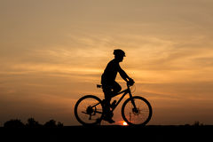 Silhouette of man and bicycle Stock Photo