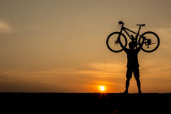 Silhouette of man and bicycle Stock Photography