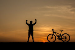 Silhouette of man and bicycle Stock Photos