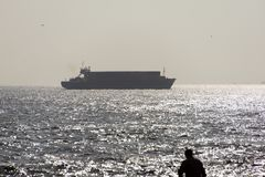 A silhouette of a man and a big tanker with containers on the sea Stock Photo