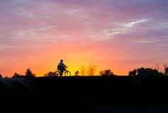 Silhouette of a man on bike at sunset Stock Photos