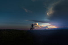 Silhouette of a man on a bike watching the sunset. Young man stops to watch dramatic sunset stock photography