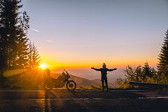 Silhouette of man biker and adventure motorcycle on the road with sunset light. Hands up. enjoy momment. Top of mountains, tourism stock photo