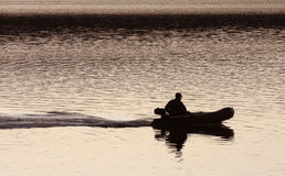 Silhouette of a man in a boat Royalty Free Stock Images