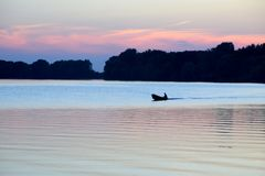 Silhouette of a man in a boat that floats in the river at sunset. A silhouette of a man in a boat that floats in the river at sunset stock images