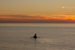 Silhouette of the man in a boat. At sunset stock photo