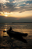 Silhouette of a man in a boat Stock Images